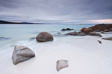 tasmanian beach at twilight with interesting rocks in the foreground (binalong bay,tasmania,australia)