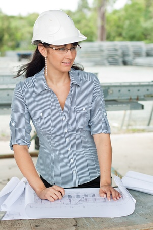 smiling young engineer woman read drawings and looks aside who wears glasses and helmet in the warehouse photo