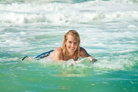 young attractive woman bodyboards on surfboard with nice smile photo
