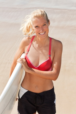 young attractive surfer woman smiles on the beach and looking up photo