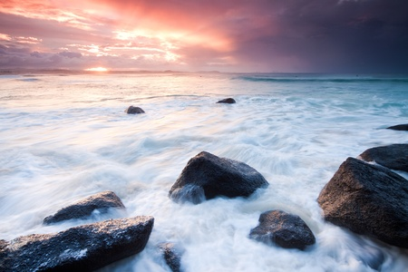 australian seascape during sunset with rushing wave in foreground (rainbow bay beach,tweed heads,nsw) Stock Photo
