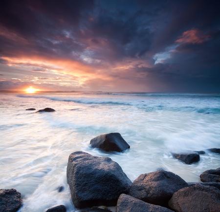 strand australie: Australische marine tijdens de schemering met stenen op de voorgrond (regenboog baai, Tweed Heads, Zuid-Holland)