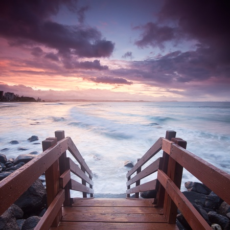 australian seascape during twilight with stairs leading towards the ocean in foreground (rainbow bay beach,tweed heads,nsw)