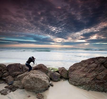 tripod: woman photographer takes photo of the beautiful seascape (miami beach, queensland, australia) Stock Photo