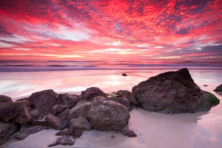 australian seascape at sunrise with rich in red color cloud formation (miami beach,queensland,australia)