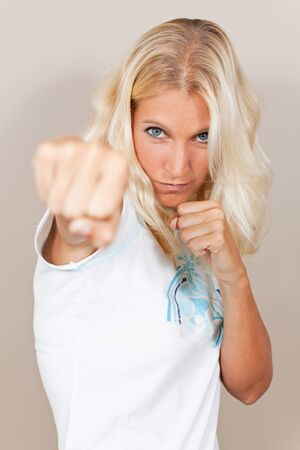 young attractive woman attacks with a punch with serious expression photo