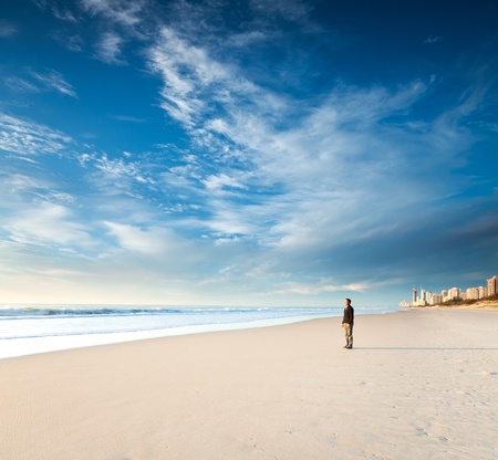 lonely man stands on the beach looks towards the sun light (gold coast, queensland, australia)