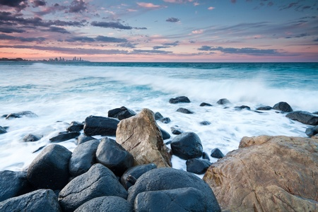 australian seascape during the twilight with rocks in foreground (rainbow bay beach,tweed heads,nsw)
