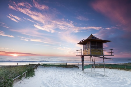 lifeguard hut on australian beach at sunrise with interesting clouds in background (gold coast, queensland, australia)
