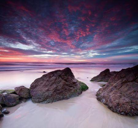 strand australie: Australische zeegezicht bij dageraad met stenen in voorgrond (miami beach, queensland, Australië) Stockfoto