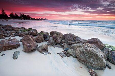 australian seascape at dawn with rocks in foreground (miami beach, queensland, australia) photo