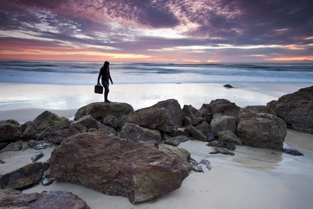 australia landscape: woman is holding his laptops bag when standing on top of the rock at dawn (miami beach,queensland,australia)