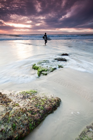 australian seascape at dawn with surfer in background (miami beach, queensland, australia) Stock Photo