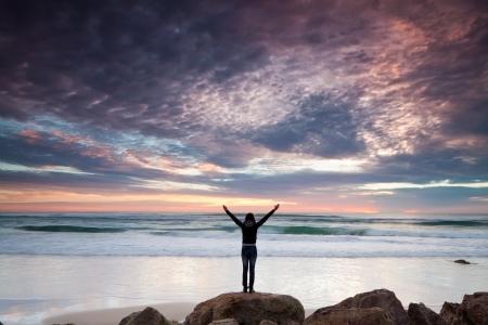 Frau steht auf Felsen vor dem Meer mit ihren Händen bei Sonnenaufgang (Gold Coast, Australien)