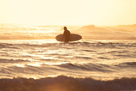 qld: surfer walks in to the water for his morning session in Burleigh Heads  Gold Coast, QLD, Australia  Stock Photo