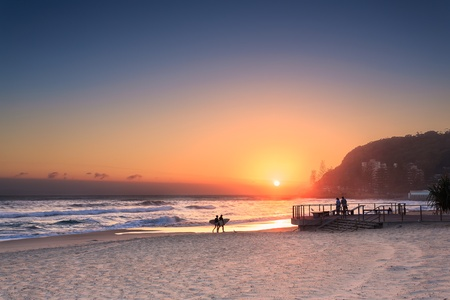 coulpe surfers walks along the beach in Burleigh Heads (Gold Coast, QLD, Australia)