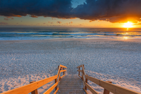 Australian beach entry with stairs in foreground at sunrise (Gold Coast, Mermaid Beach, QLD, Australia)