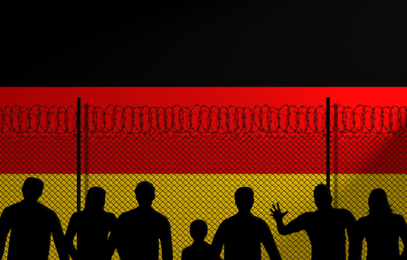 People in front of a secured fence. German flag behind.