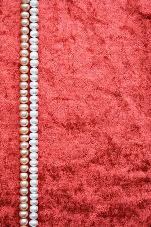 White and pink pearls on the terracotta velvet can use as background photo