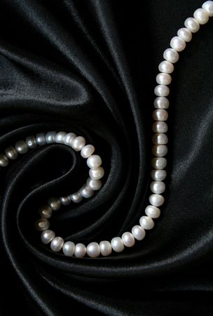 White pearls on the black silk can use as background photo