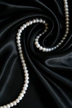 White pearls on the black silk can use as background Stock Photo - 5219267