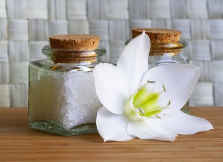 Bottles of sea salt and oil with white flower in spa composition  photo