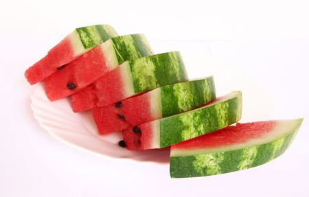 Slices of juicy watermelon served on a white plate isolated on white background  photo