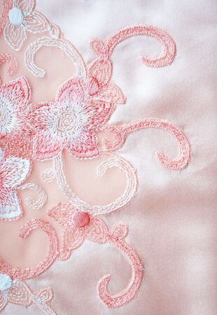 Flower lace on the elegant pink silk can use as wedding background photo