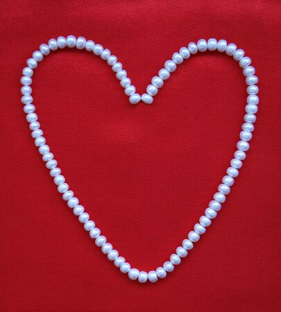 Heart from white pearls on an elegant red silk for St Valentines day card photo
