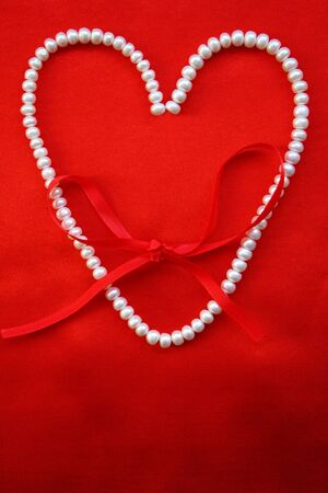 Heart from white pearls on a red silk for St Valentines day  photo