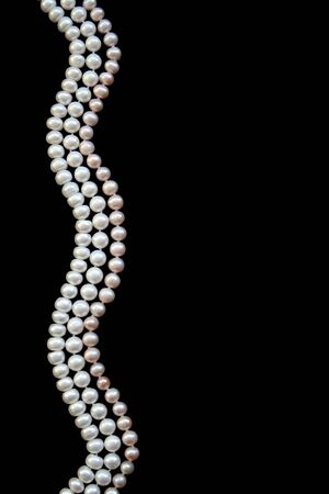 White and pink pearls on the black silk as background  photo