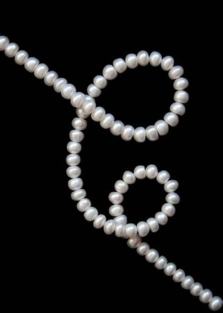 White pearls on the black silk as background  photo