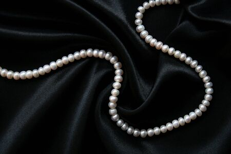 White pearls on the black silk as background  Stock Photo - 6359036