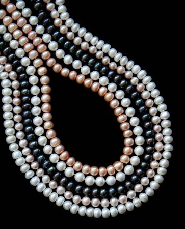 White, black and pink pearls on the black silk as background Stock Photo - 6362569