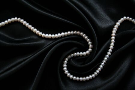 White pearls on the black silk as background