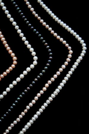 White, black and pink pearls on the black silk as background  Stock Photo - 6391054