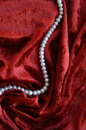 Necklace of white pearls on a terracotta velvet as background  photo
