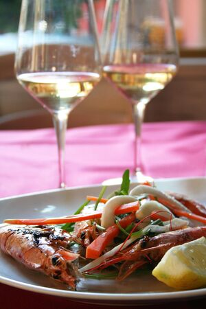 Italy. Liguria. Cinque Terre. Royal shrimps fried on a grill with vegetables and two bocals of white wine