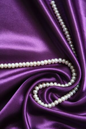 White pearls on a lilac silk as background  photo