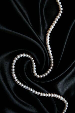 White pearls on the black velvet background  photo