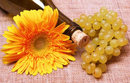 Wine bottle with yellow flower and grapes branch Stock Photo - 8019652