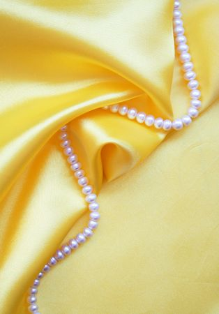 Smooth elegant golden silk with pearls can use as background