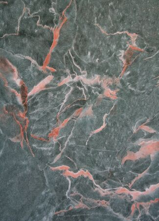 Artificial green marble texture with orange and white lines as background photo