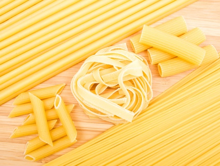 Different kinds of italian pasta on the wooden background  photo
