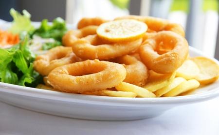 calamar: Bateador profunda frito calamares de anillos de calamar con ensalada verde en plato blanco