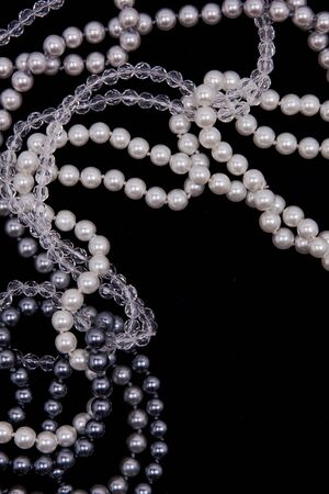 White, black and grey pearls on the black silk background