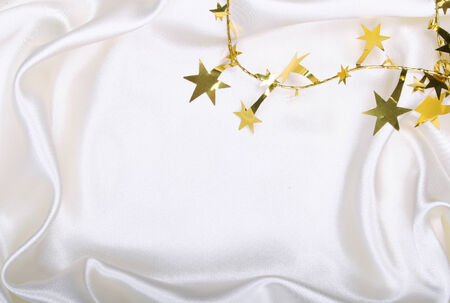 spangles: Golden stars and spangles on white silk as background Stock Photo