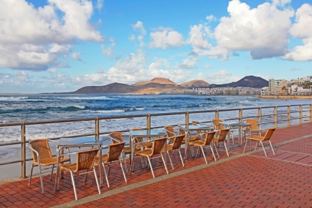 Spain. Canary Islands. Gran Canaria island. Las Palmas de Gran Canaria city. An open-air cafe on the Las Canteras beach at sunset photo