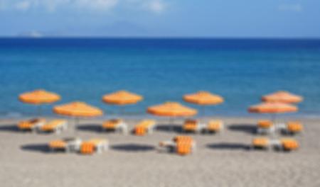 orange chairs: Greece. Kos island. Kefalos beach. Orange chairs and umbrellas on the beach. In blur style