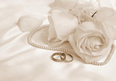 anillo de compromiso: Los anillos de boda y rosas como telón de fondo Foto de archivo